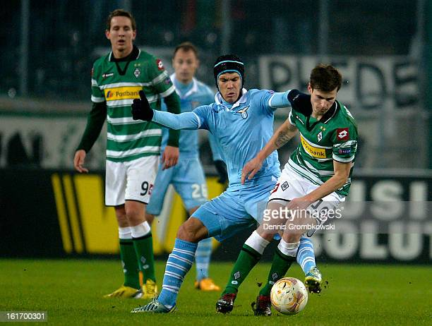 Hernanes of Lazio challenges Havard Nordtveit of Moenchengladbach during the UEFA Europa League round of 32 first leg match between VfL Borussia...