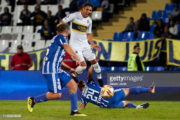 Hernán Bernardello and Kevin Gutiérrez of Godoy Cruz Emanuel Reynoso of Boca Juniors during a first leg round of sixteen match between of Godoy Cruz...