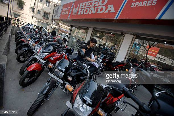 Hero Honda Motors Ltd employee takes stock of parked motorcycles at a showroom in Mumbai India on Tuesday Jan 15 2008 Hero Honda sold 240532...