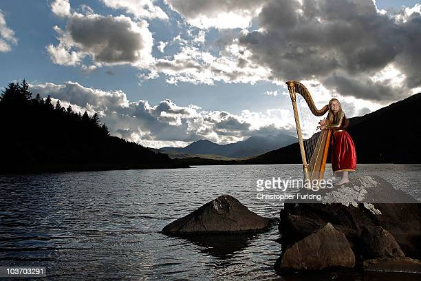 Hero Melia aged eleven poses as she sings and plays her harp to tourists near her home in the mountains of Snowdonia on August 27 2010 in Capel Curig...