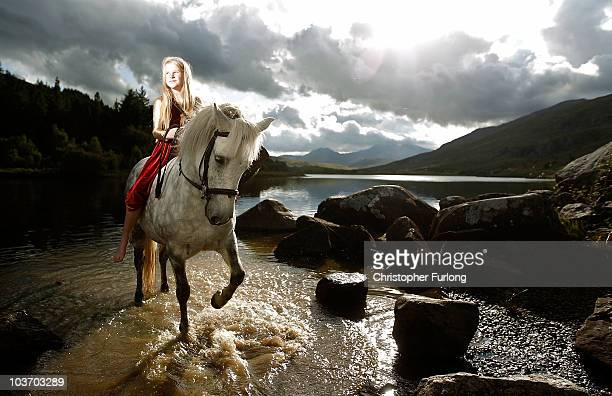 Hero Melia aged eleven poses with her pony Quince as she sings and plays her harp to tourists near her home in the mountains of Snowdonia on August...