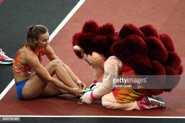 Hero the Hedgehog helps Nadine Visser of the Netherlands with her cleats after she competed in the Women's 100 metres hurdles semi finals during day...