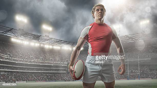 Heroic Rugby Player Standing With Ball In Floodlit Stadium