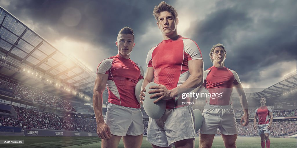 Heroic Rugby Players Standing With Ball On Pitch In Stadium : Stock Photo