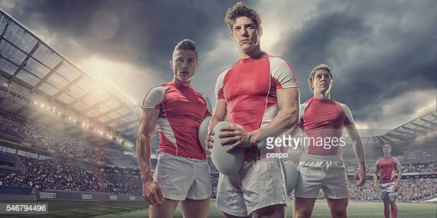 heroic rugby players standing with ball on pitch in stadium - rugby stock-fotos und bilder