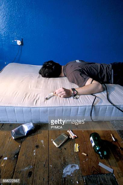 A heroin addict crashed out on a mattress surounded by syringes and drinks cans UK 1990s