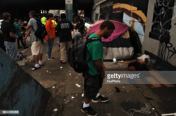 A heroin addict nods amid the chaos of the eviction of a homeless encampment in the Kensington section of Philadelphia on May 30 2018