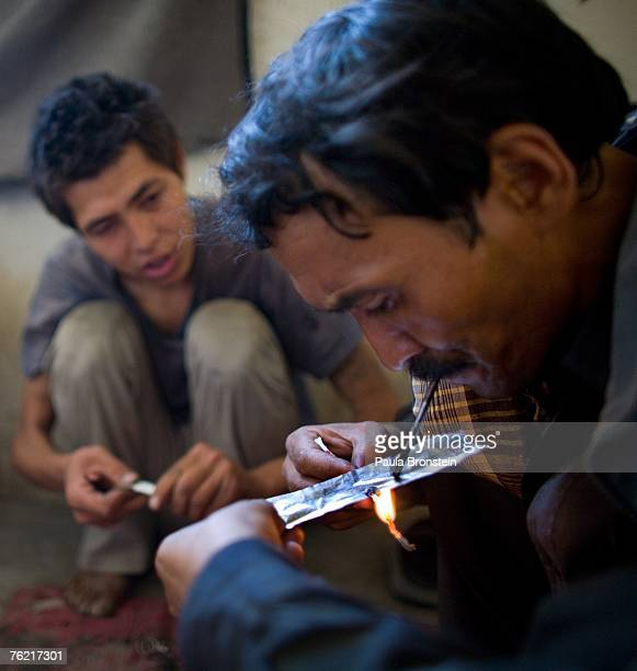 Heroin addicts smoke in an abandoned building August 22 2007 in Kabul Afghanistan The cost for daily use is around $300 USD or 150 Afghan currency...