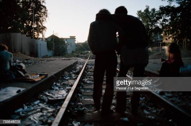 Heroin addicts walk along the tracks at Letten Station an abandoned railroad station in Zurich Switzerland where the city's new liberal drug policy...