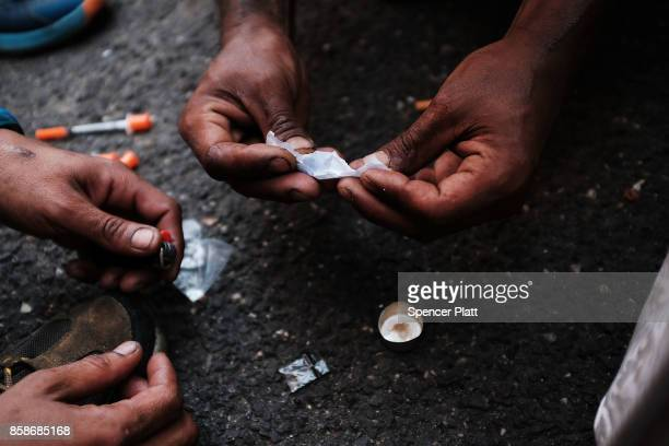 Heroin users prepare to shoot up on the street in a South Bronx neighborhood which has the highest rate of heroininvolved overdose deaths in the city...