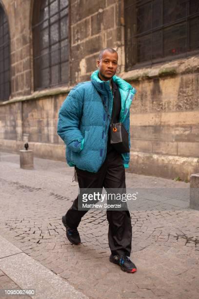 Heron Preston is seen on the street during Paris Men's Fashion Week wearing turquoise down jacket, Louis Vuitton bag with Heron Preston sneakers on...