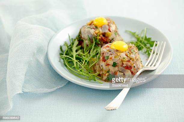 Herring tartar with dried tomatoes, pickled gherkins and quail's eggs