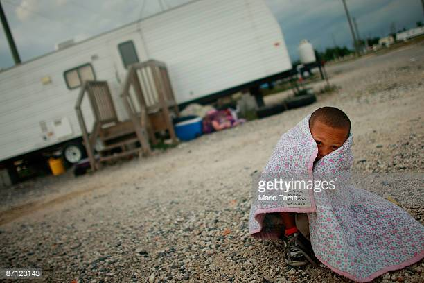 Herschel Barthelemy sits outside the FEMA trailer he lives in with six other children May 11, 2009 in Port Sulphur, Louisiana. Seven children from...