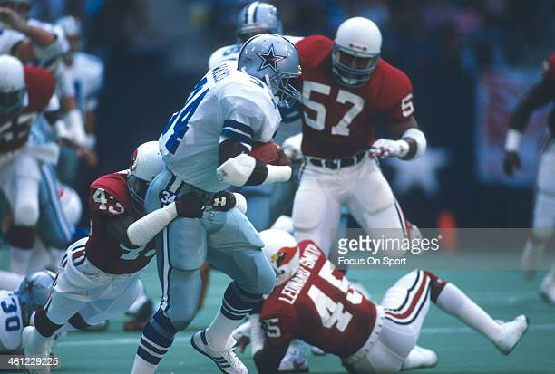 Herschel Walker of the Dallas Cowboys gets wrapped up from behind by Lonnie Young of the Phoenix Cardinals during an NFL football game October 29,...