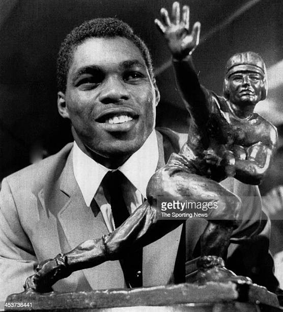 Herschel Walker of the University of Georgia Bulldogs poses with his Heisman Trophy at the Downtown Athletic CLub circa 1982 in New York City