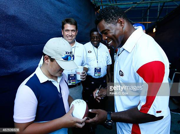 Herschel Walker signs an autograph prior to the match between Nathan Pasha and Lukas Lacko of Slovakia during the BBT Atlanta Open at Atlantic...
