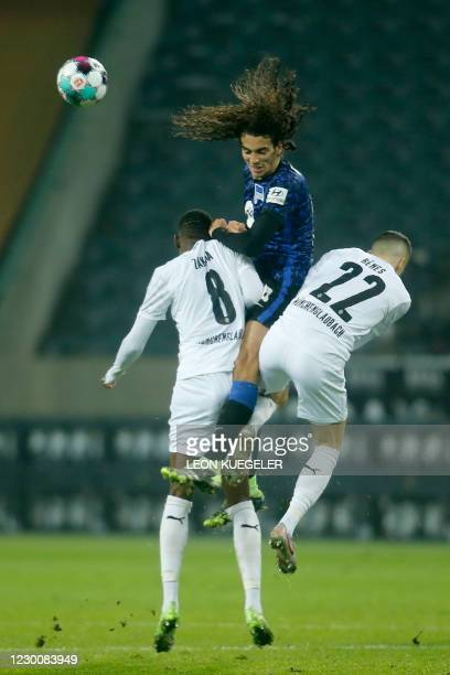 Hertha Berlin's French midfielder Matteo Guendouzi vies for the ball with Moenchengladbach's Swiss midfielder Denis Zakaria and Moenchengladbach's...