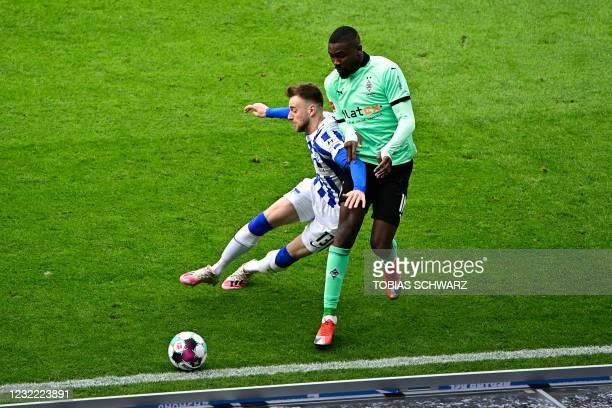 Hertha Berlin's German defender Lukas Kluenter and Moenchengladbach's French forward Marcus Thuram vie for the ball during the German first division...
