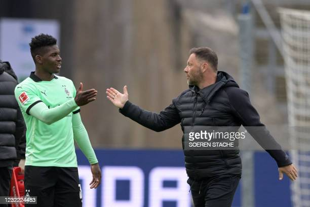 Hertha Berlin's Hungarian head coach Pal Dardai shakes hands with Moenchengladbach's Swiss forward Breel Embolo after the German first division...