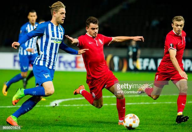 Hertha Berlin's midfielder Arne Maier Zorya's defender Artem Sukhotskiy and Zorya's midfielder Dmytro Grechyshkin vie for the ball during the UEFA...