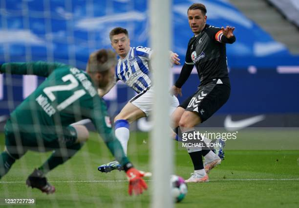 Hertha Berlin's Polish forward Krzysztof Piatek scores the opening goal past Freiburg's German goalkeeper Florian Mueller during the German first...