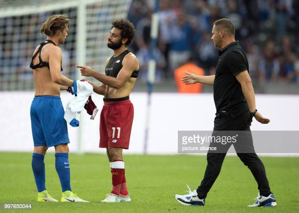 Hertha's Valentin Stocker and Liverpool's Mohamed Salah swap shirts at the end of the international club friendly soccer match between Hertha BSC and...