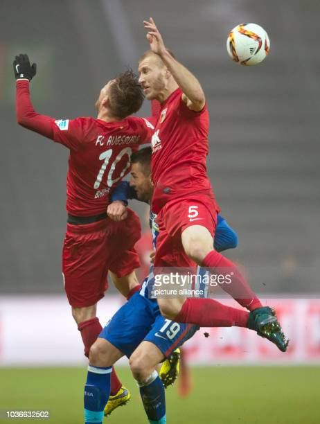 Hertha's Vedad Ibisevic competes for the ball against Augsburg's Daniel Baier and Ragnar Klavan during the German Bungesliga football match between...