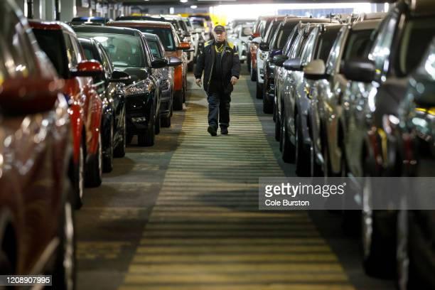 Hertz Car Rental employee walks between rows of unused rental cars at Toronto Pearson International Airport on April 1 2020 in Toronto Canada Air...