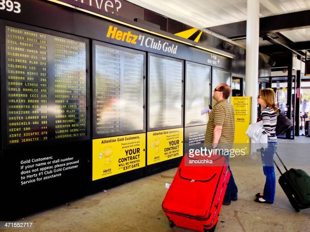 hertz customers looking at their names on schedule - hertz car stock pictures, royalty-free photos & images