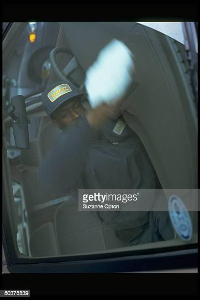 Hertz RentaCar worker wiping down dashboard of car