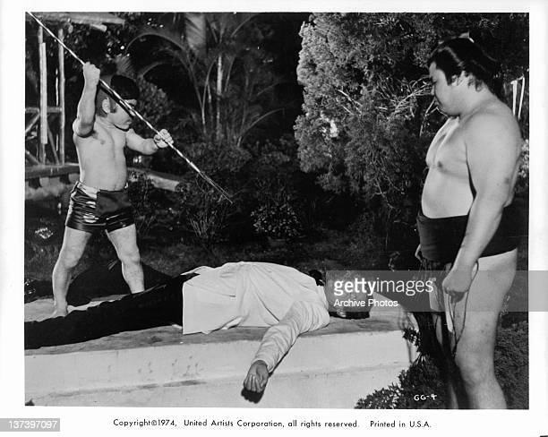 Hervé Villechaize holding a spear over actor Roger Moore as James Bond who is lying on slab of cement in a scene from the film 'The Man With The...