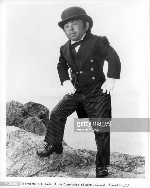 Hervé Villechaize standing on a cliff in a tuxedo gloves and hat in a scene from the film 'The Man With The Golden Gun' 1974