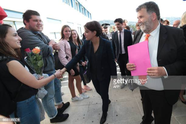 Herve Pizzinat head teacher of the Alexis de Tocqueville high school looks on as French Education Minister Najat VallaudBelkacem greets students...