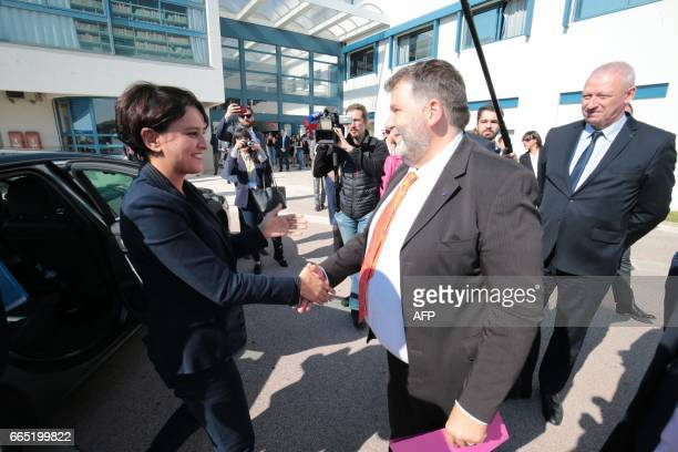Herve Pizzinat head teacher of the Alexis de Tocqueville high school shakes hands with French Education Minister Najat VallaudBelkacem as she arrives...