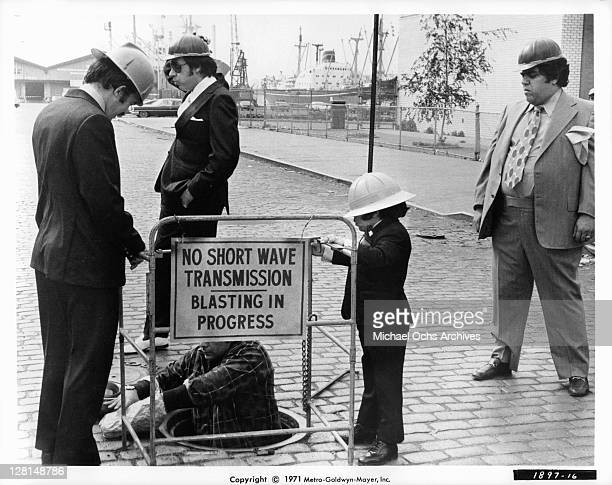 Herve Villechaize in a hard hat as well as three unknown actors in a scene from the film 'The Gang That Couldn't Shoot Straight' 1971