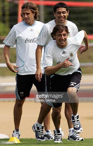 Herzogenaurach, GERMANY: Argentinean defender Gabriel Heinze starts running while midfielder Juan Roman Riquelme and forward Hernan Crespo wait their...