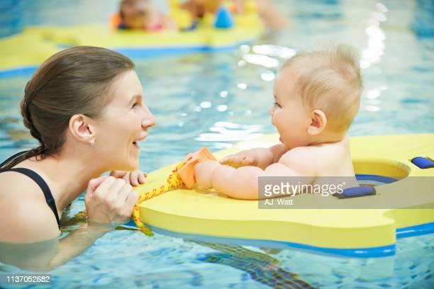 er genießt ihren ersten sprung in den pool - schwimmen stock-fotos und bilder