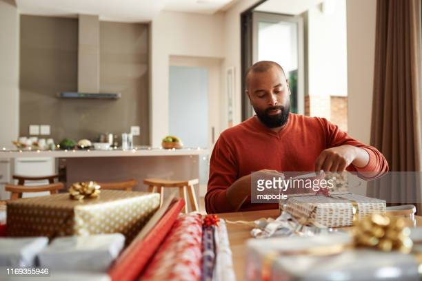 he's got gift wrapping duties covered - wrapping stock pictures, royalty-free photos & images