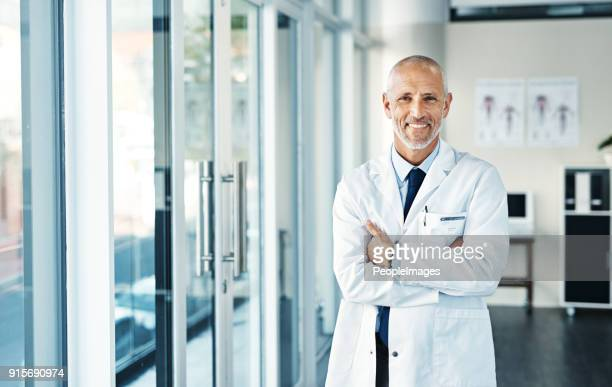he's got years of experience behind his name - male doctor stock photos and pictures