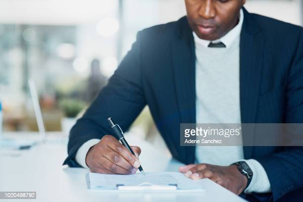 he's the one who signs off on all important tasks - form filling stock photos and pictures