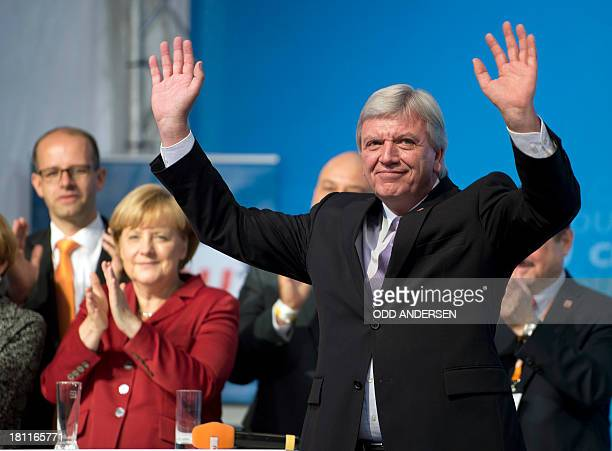 Hesse premier Volker Bouffier is applauded by German Chancellor Angela Merkel after speaking at an election campaign event of her German Christian...