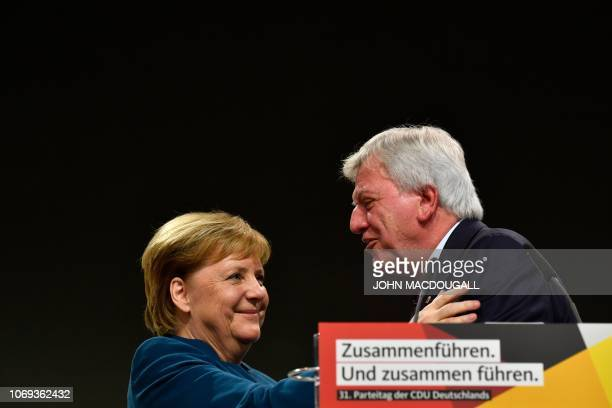 Hesse's State Premier and Deputy Chairman of the Christian Democratic Union Volker Bouffier embraces German Chancellor and leader of the Christian...