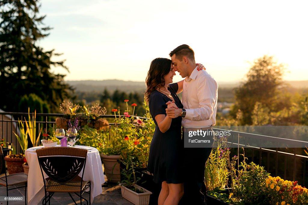 Heterosexual couple dancing after a romantic dinner on a veranda : Stock Photo
