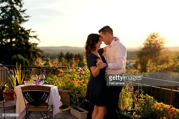 Heterosexual couple dancing after a romantic dinner on a veranda