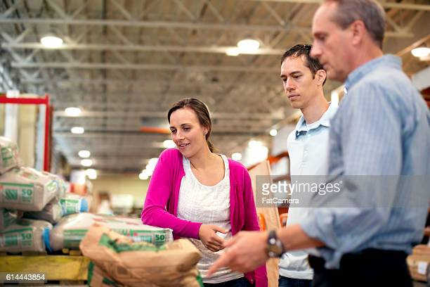 Heterosexual couple getting advice from a hardware store employee