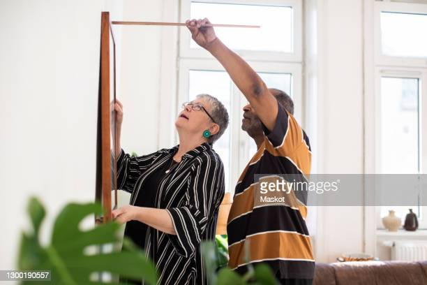 heterosexual couple measuring painting while hanging on wall in living room - hanging stock pictures, royalty-free photos & images