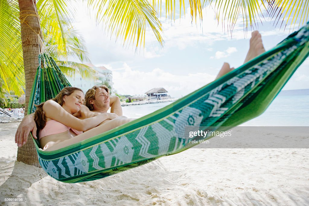Heterosexual couple relaxing in hammock on beach : Stockfoto