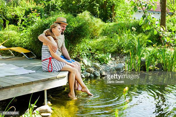 Heterosexual couple takes a break by the pond, rear view, Munich, Bavaria, Germany