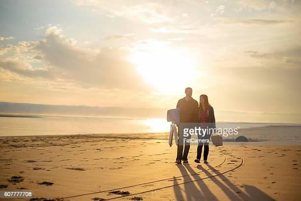 Heterosexual couple walking at sunset at the beach