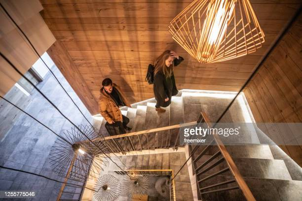 heterosexual couple walking upstairs after check in on hotel reception - staircase stock pictures, royalty-free photos & images